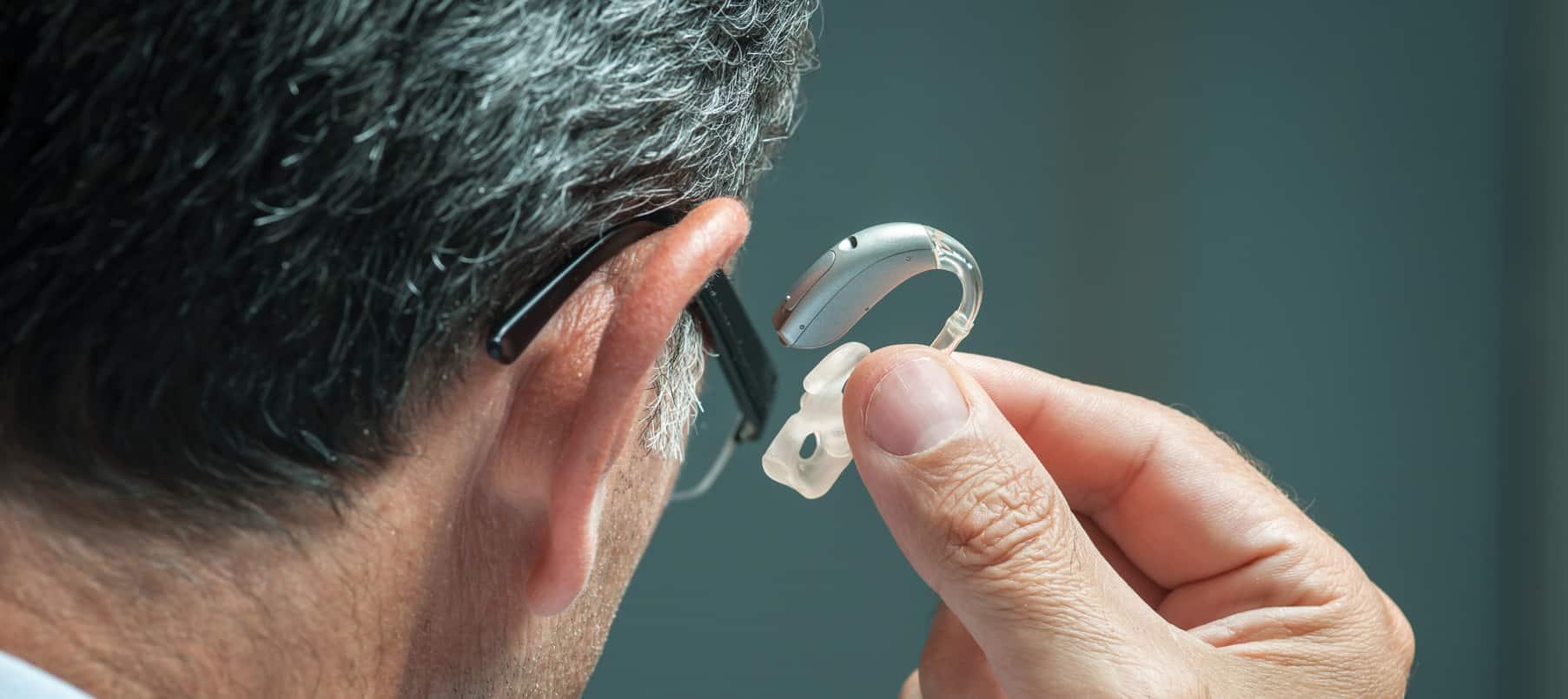 Un homme entrain d'admirer une prothèse auditive